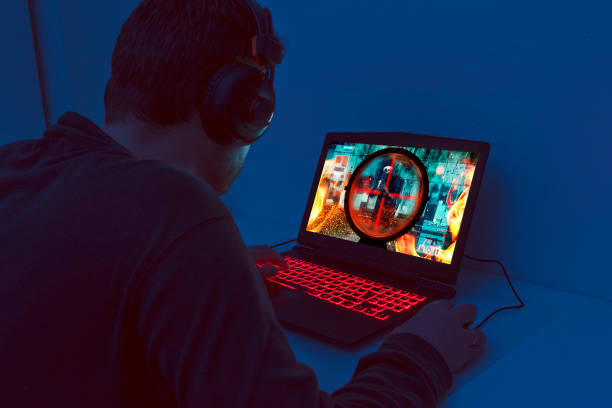 action video game plays out on gaming laptop at night - esports stock photos and pictures