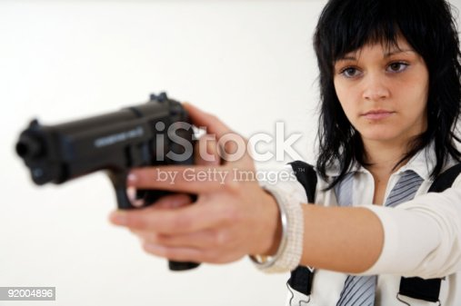 A young woman with gun on white background. Shot with shallow DOF focused on the woman face.