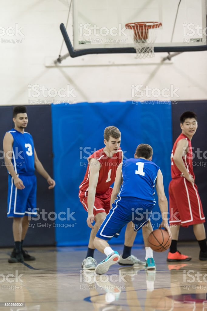 A high school basketball player dribbles cautiously as he looks for a...