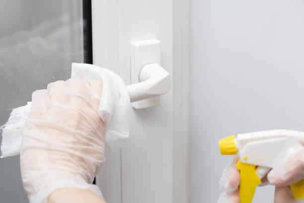 Maßnahmen zur Verhinderung der Ausbreitung des Coronavirus KOVID-19, Desinfektion des Türgriffs. Hand in Handschuhe nwipet den Türgriff mit einem Desinfektionsmittel – Foto