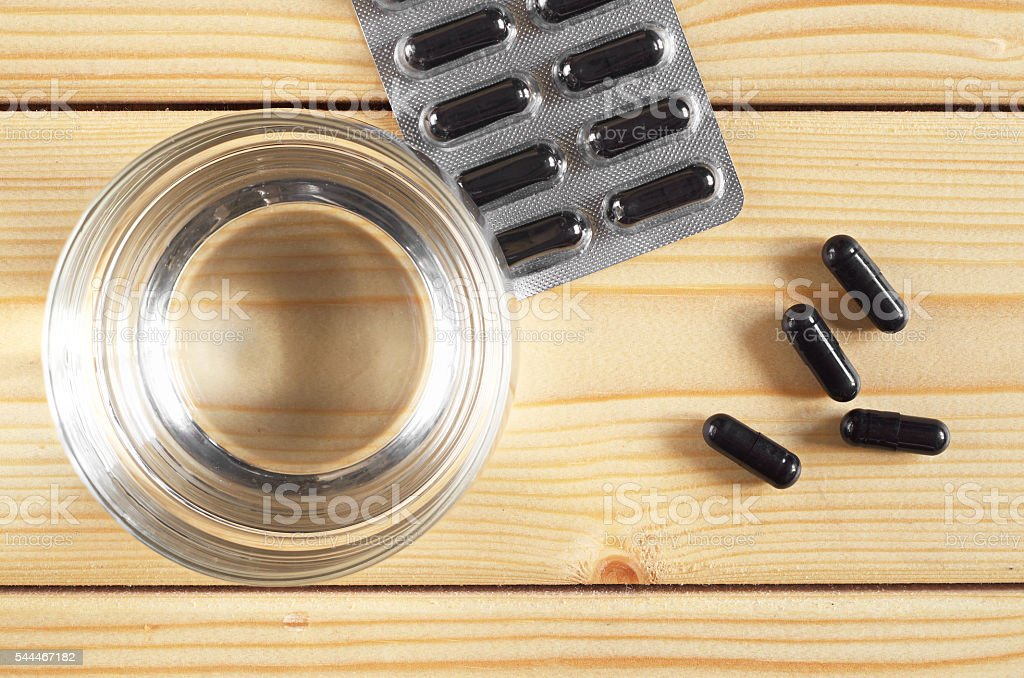 Activated charcoal and glass of water stock photo