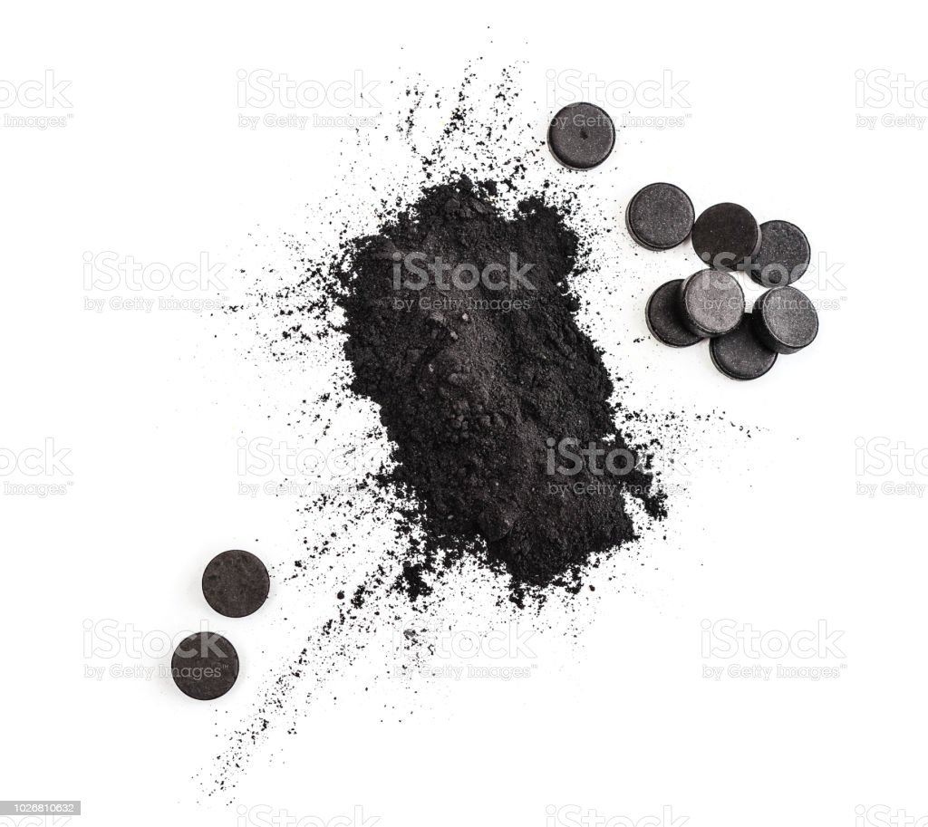 Activated charcoal in powder and in pills stock photo