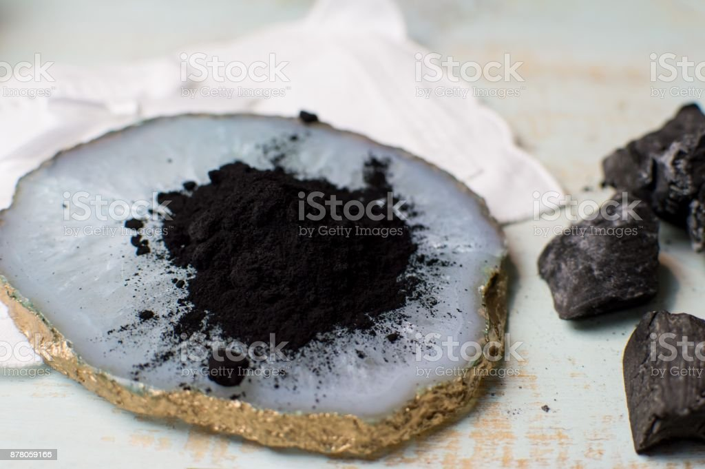 Activated charcoal powder beauty detox background stock photo
