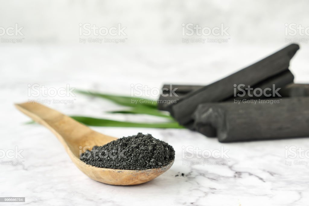 Activated charcoal powder on marble table. stock photo