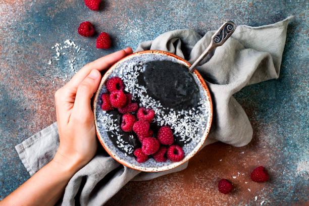 aktivkohle-smoothie und chia samen schüssel pudding, veganen detox dessert mit himbeeren und kokosmilch. overhead, top aussicht, flach zu legen - chia samen pudding stock-fotos und bilder