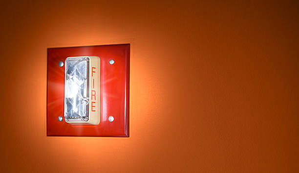 Activated Red Glowing Fire Alarm Signal on Wall stock photo
