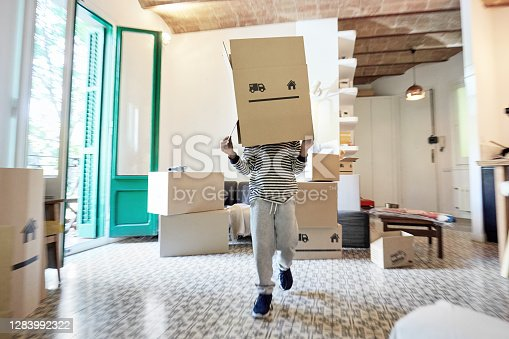 Full length front view of young boy in casual clothing having fun as he runs toward camera with cardboard box over his head in home interior.