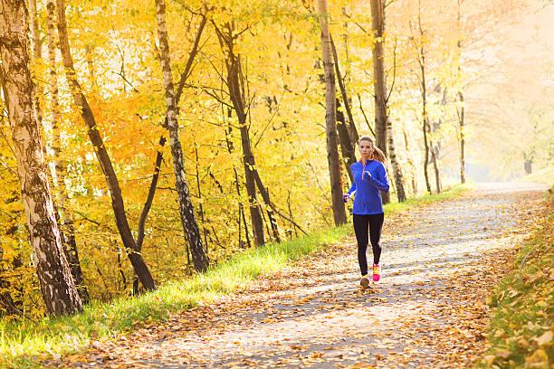 aktive und sportliche frau läufer im herbst natur - joggerin stock-fotos und bilder