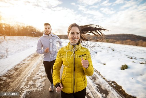 istock Active athletes sportive couple running with strong persistence on the road in winter nature in the morning. 941224800