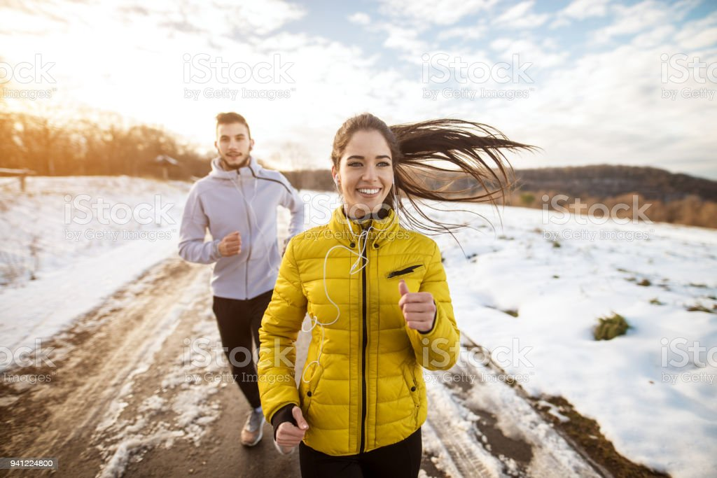 Active athletes sportive couple running with strong persistence on the road in winter nature in the morning. stock photo
