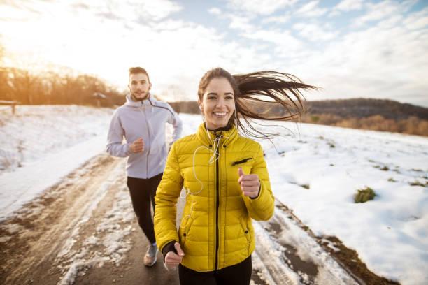 aktive sportler sportliche paar mit starker ausdauer auf die straße im winter natur morgens ausgeführt. - kalte sonne stock-fotos und bilder