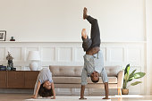 Sporty active african American father and preschooler daughter have fun practice gymnastics in living room, happy biracial dad and little girl child have fun play do exercised at home together