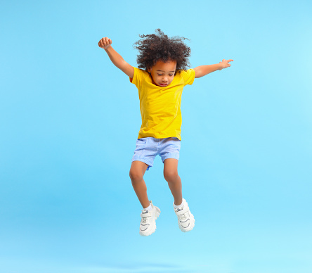Full length of energetic little ethnic boy with Afro hairstyle in stylish casual outfit jumping with raised arms and looking down against blue background