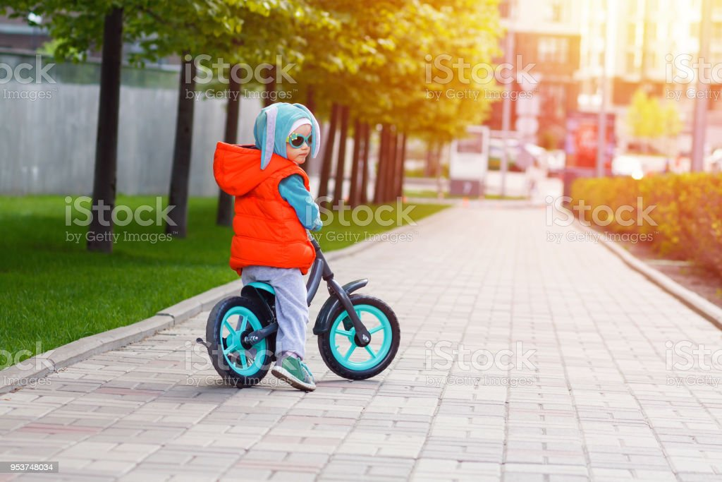 Active blond kid driving run bike the street alley of the city. Funny...