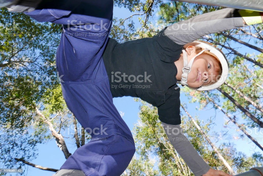 Active boy climbing on bars with forest background stock photo