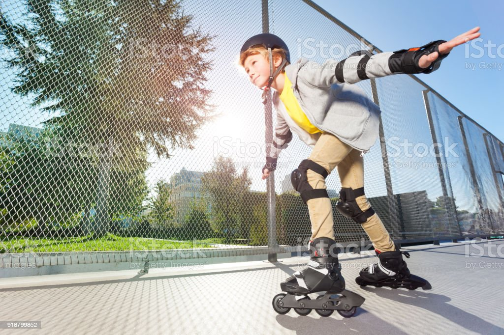 Active boy in helmet rollerblading at skate park stock photo
