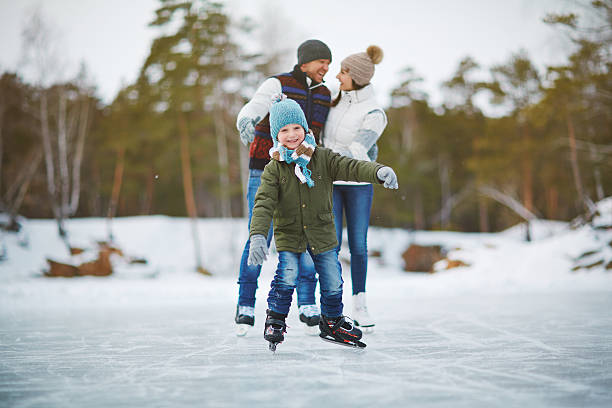 Active boy Happy boy on skates looking at camera with his parents behind recreational pursuit stock pictures, royalty-free photos & images