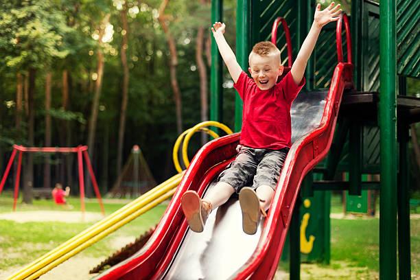 Active boy sliding down stock photo