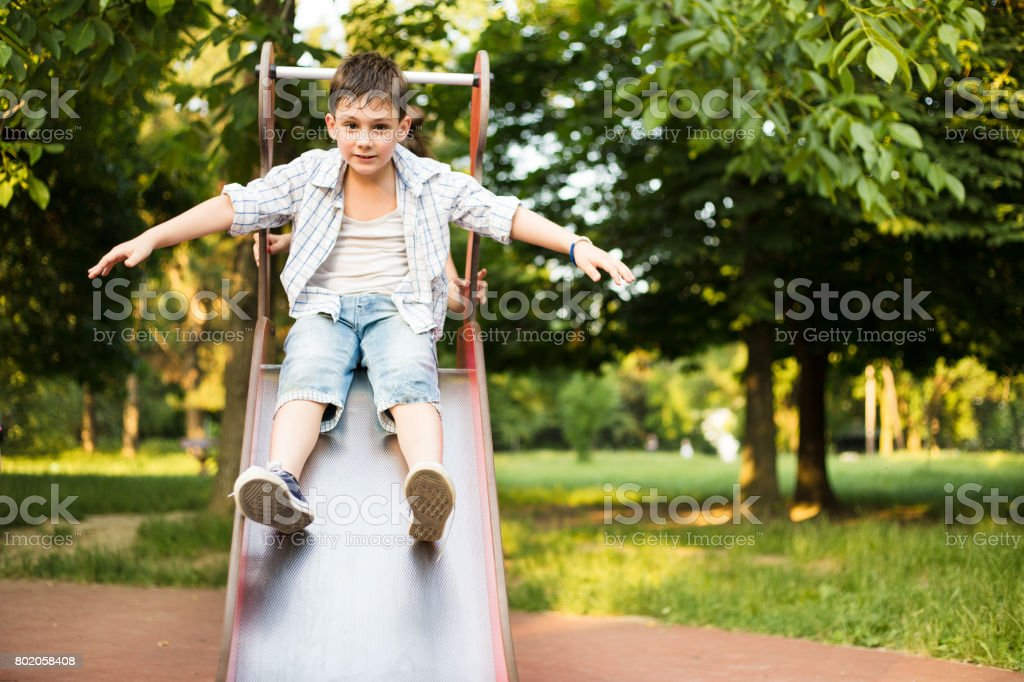 Active boy sliding down stock photo