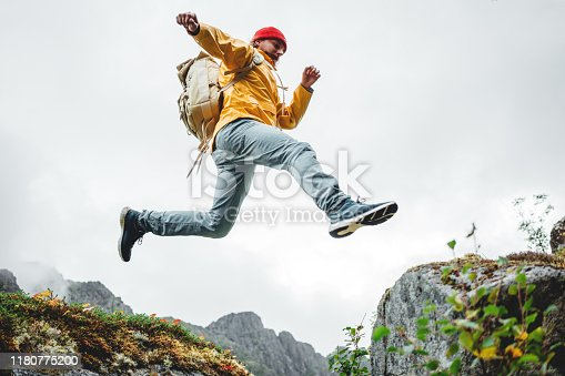 Active brave tourist jumping through cliff in mountain lifestyle outdoor journey. Man traveler with rucksack hiking mountains wilderness