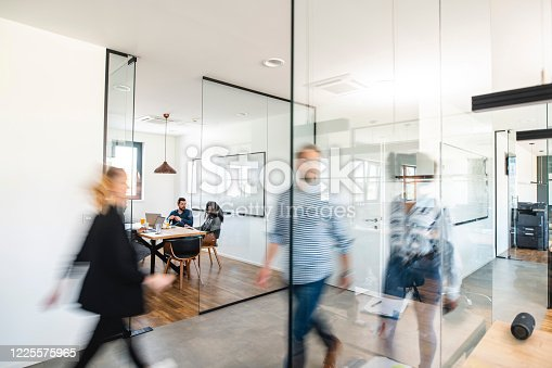 Blurred motion of energetic businesspeople on the go and project team members discussing ideas in a conference room.