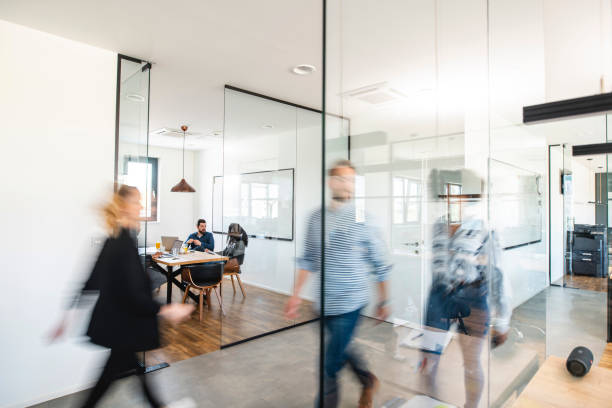 Active Business Colleagues and the Development of Ideas Blurred motion of energetic businesspeople on the go and project team members discussing ideas in a conference room. office stock pictures, royalty-free photos & images
