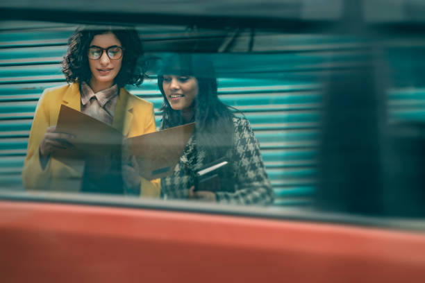 Active businesswomen discuss project by the side of busy road. stock photo
