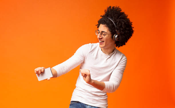 Active carefree black guy in wireless headphones enjoying music Active carefree black guy in wireless headphones enjoying music online on smartphone and dancing, orange background wireless headphones stock pictures, royalty-free photos & images