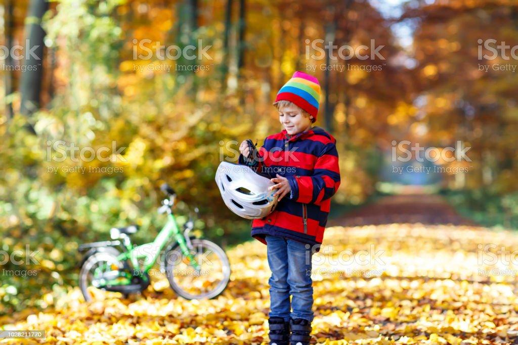 Aktives Kind, sicheren Helm bevor Radfahren auf sonnigen Herbsttag in der Natur. – Foto