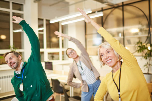 Active company employees exercising in office stock photo