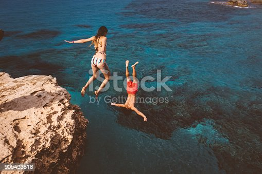 istock Active couple diving from high cliff into ocean 905493816