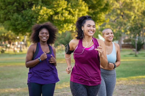 Active curvy women jogging Group of curvy girls friends jogging together at park. Beautiful smiling young women running at the park on a sunny day. Female runners listening to music while jogging. exercising stock pictures, royalty-free photos & images