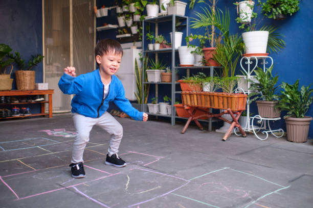 aktive niedlich lächelnde asiatische kleinkind junge spaß beim springen, hopscotch zu hause spielen - himmel und hölle spiel stock-fotos und bilder