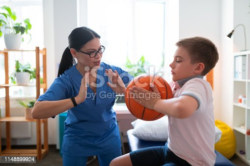 istock Active dark-haired nurse in blue uniform showing example 1148899924