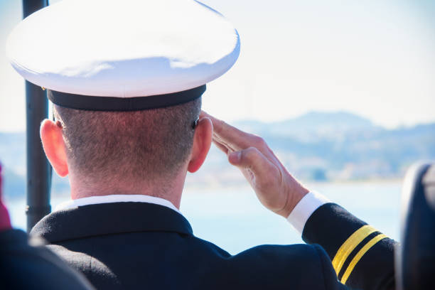 active duty u.s. naval officer saluting - navy stock photos and pictures
