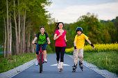 Summer joy - family running, biking, roller-blading outdoor