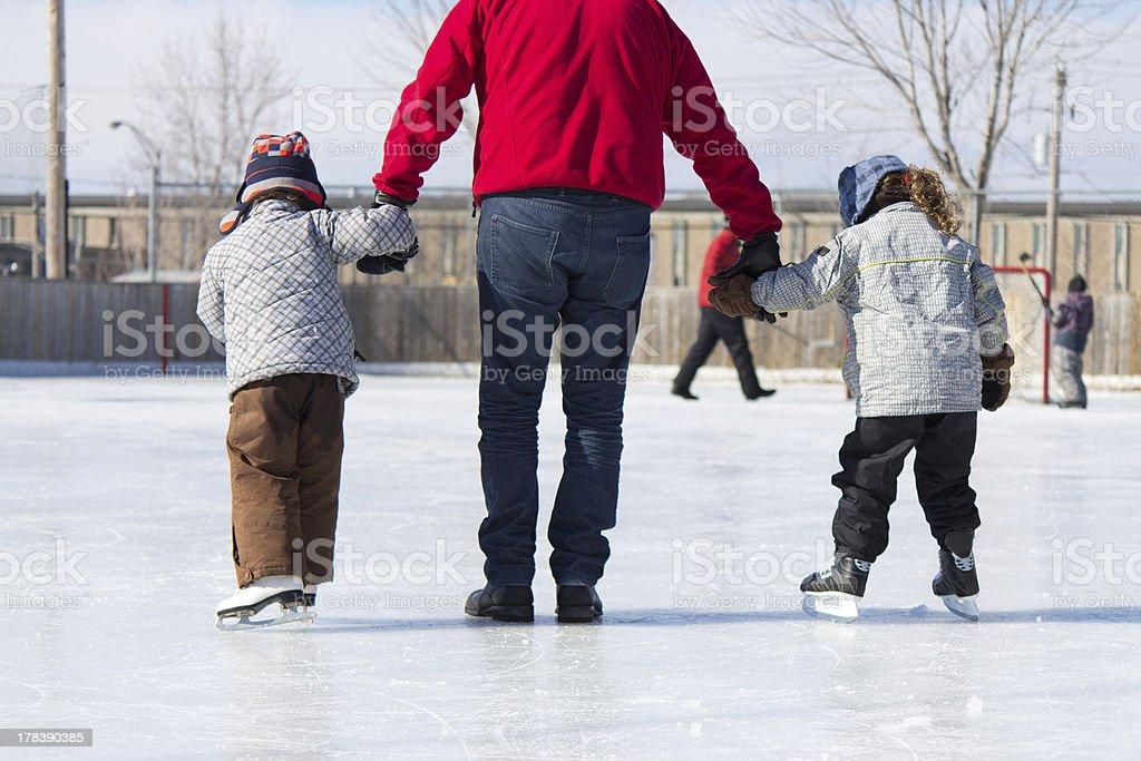 Active family having winter fun at the ice skating rink stock photo
