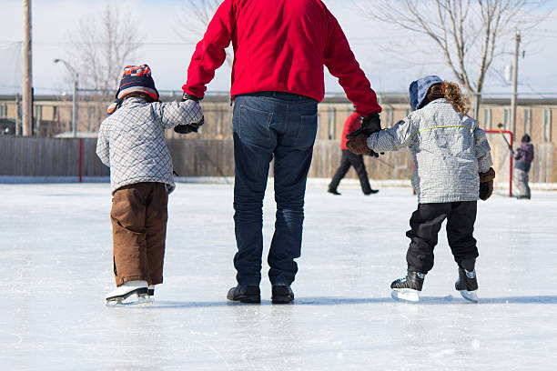Active family having winter fun at the ice skating rink stock photo