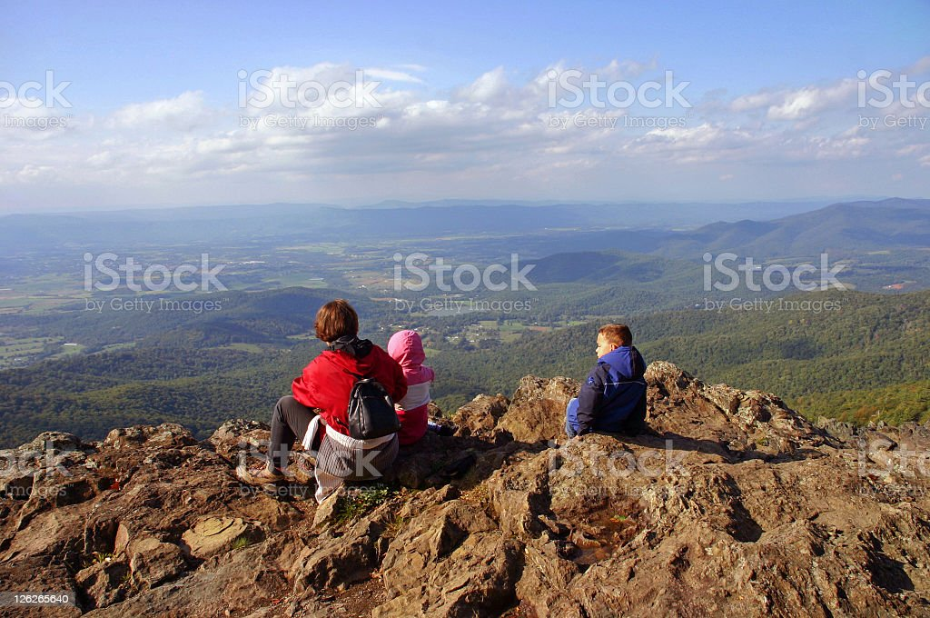 Active family - parent and children hiking/sitting on mountain royalty-free stock photo
