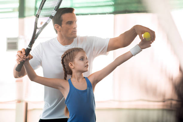 Active family playing tennis on court stock photo