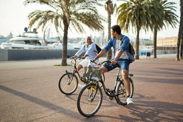 Active Father and Adult Son Spending Outdoor Time Together Carefree mixed race male family members in early 20s and late 40s enjoying cycling while vacationing in Barcelona. Bike rental stock pictures, royalty-free photos & images