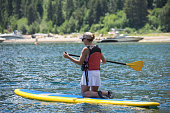 Active fit woman (30s) kneels on a stand up paddleboard on Lake Tahoe in the summer.