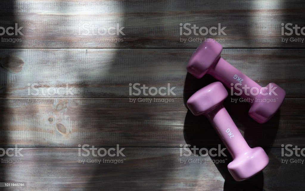 Active fitness lifestyle and exercise background concept. Pink dumbbell on wooden with light and shadow. Top view. stock photo