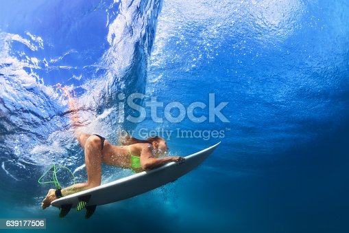 583830686 istock photo Active girl in bikini in dive action on surf board 639177506