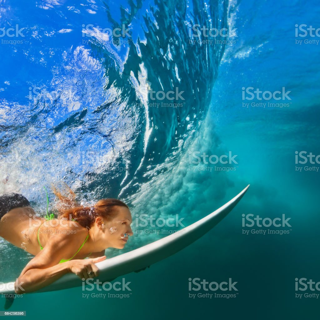 Active girl in bikini in dive action on surf board stock photo