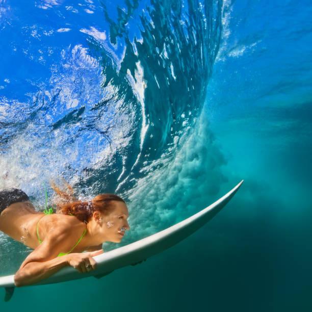 Active girl in bikini in dive action on surf board stock photo