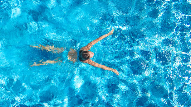 Active girl in swimming pool aerial drone view from above, young woman swims in blue water, tropical vacation, holiday on resort concept stock photo