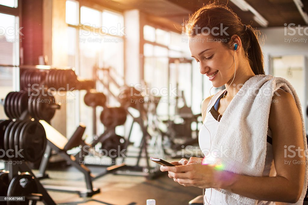 Active girl using smartphone in fitness gym. stock photo