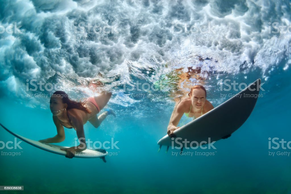 Active girls in bikini in dive action on surf board stock photo
