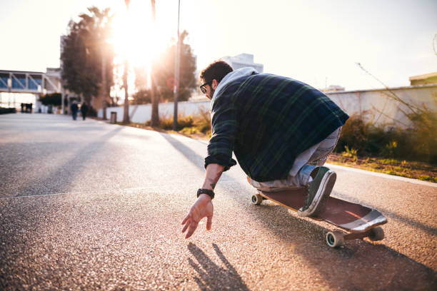 Active hipster man skateboarding and having fun in the city Fashionable professional skateboarder skateboarding with longboard in city park eurasia stock pictures, royalty-free photos & images